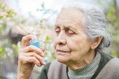 Elderly woman having asthma attack, holding a bronchodilator Stock Photography