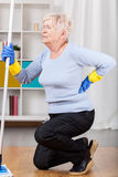 Elderly woman having back pain. While cleaning Stock Image