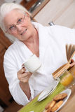 Elderly woman having breakfast Royalty Free Stock Photo
