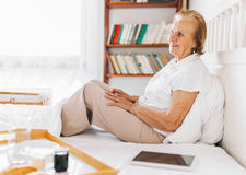 Elderly woman having breakfast in bed whilst using her tablet Stock Photography