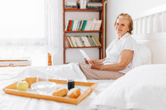 Elderly woman having breakfast in bed whilst using her tablet Royalty Free Stock Images