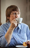 Elderly woman having coffee and cookie Royalty Free Stock Photography