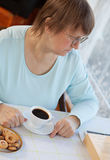 Elderly woman having coffee with cookies Stock Photo