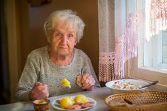 Elderly woman is having dinner sitting at the table alone. Stock Image