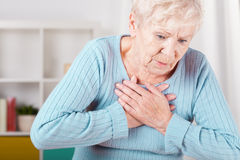 Elderly woman having heart attack stock photos