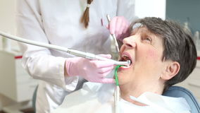 Elderly woman having her teeth fixed at dentist's stock footage