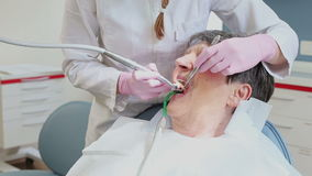 Elderly woman having her teeth fixed at dentist's stock video footage