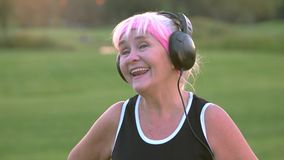 Elderly woman in headphones. Lady smiling and singing. Music and mood. Tune of my life stock footage