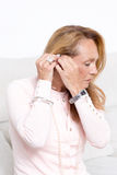 Elderly woman with a hearing aid. Hard-of-hearing woman with deaf-aid Royalty Free Stock Image