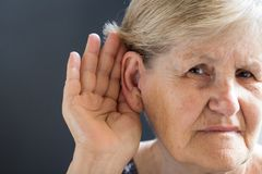 Elderly woman with hearing loss on grey background. Age related. Elderly woman with hearing problem on grey background. Age-related hearing loss, symptoms and royalty free stock photos