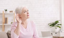 Elderly woman with hearing loss at home. Age-related hearing loss, symptoms. Senior woman listening for something at home, panorama with free space royalty free stock photo
