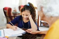 Elderly Woman Helping Little Girl Doing School Homework Stock Photo