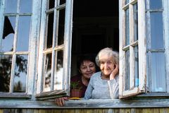 Elderly woman and her adult daughter looking out the window. royalty free stock photos
