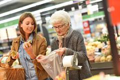 Elderly woman and her daughter at grocery store Stock Photo