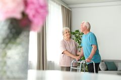 Elderly woman and her husband with walking frame royalty free stock image