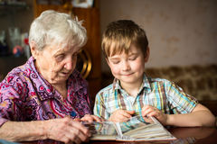Elderly woman with her little grandson looking album. Family. Stock Photo