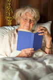 Elderly woman in her nightgown reading in bed Stock Photography