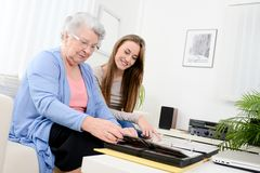 Elderly woman with her young granddaughter at home looking at memory in family photo album Stock Photo