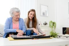 Elderly woman with her young granddaughter at home looking at memory in family photo album Royalty Free Stock Images