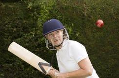 Elderly woman hitting cricket ball Royalty Free Stock Photos
