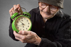 Elderly woman holding an alarm clock. Royalty Free Stock Photo