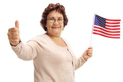 Elderly woman holding an American flag and making a thumb up sign royalty free stock photo
