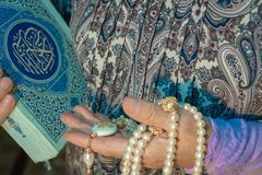 An elderly woman is holding a beautiful white rosary and the Koran. Hands of an elderly person with a holy book and pearl rosary royalty free stock images