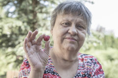 Elderly woman holding a berry fruit Stock Images