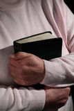 Elderly Woman Holding a Bible. Elderly woman's hands holding a Bible close to her body under dramatic lighting stock photos