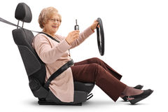 Elderly woman holding car key and sitting in car seat Royalty Free Stock Photo