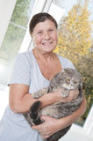 An elderly woman is holding a cat breed Scottish Fold. 