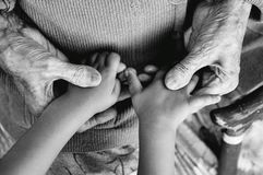 An elderly woman holding children`s hands, a wooden cane on the street. great-grandmother and great-grandson.black and white phot. An elderly woman holding stock photography