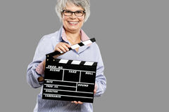 Elderly woman holding a clapboard Royalty Free Stock Photos