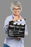 Elderly woman holding a clapboard Stock Photography