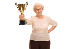 Elderly woman holding a golden trophy. Cheerful elderly woman holding a golden trophy isolated on white background royalty free stock photography