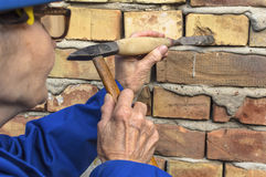 Elderly woman holding a hammer and chisel. Elderly woman holding a hammer and chisel, selective focus stock photos