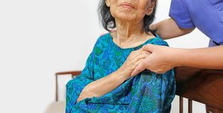Elderly woman holding hand with caregiver royalty free stock image