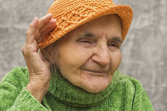 Elderly woman holding hand close to an ear. Royalty Free Stock Images