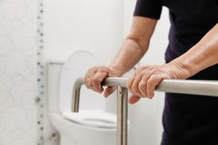 Elderly woman holding on handrail in toilet. Elderly woman holding on handrail in bathroom royalty free stock images