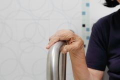 Elderly woman holding on handrail in toilet. Elderly woman holding on handrail in bathroom stock image