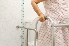 Elderly woman holding on walker in toilet. royalty free stock image