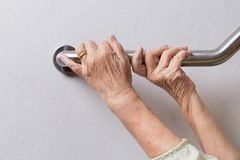 Elderly woman holding on handrail for safety steps. Elderly woman holding on handrail for safety walk steps royalty free stock photo