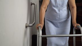 Elderly woman holding on handrail for safety walk.