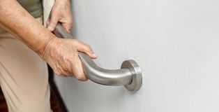 Elderly woman holding on handrail for safety walk steps. Close up Elderly woman holding on handrail for safety walk steps royalty free stock photography