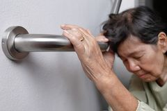 Elderly woman holding on handrail for safety walk. Steps stock photos