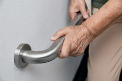 Elderly woman holding on handrail for safety walk steps. Elderly woman holding on handrail for safety walk stair steps stock photography
