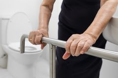 Elderly woman holding on handrail in toilet. Elderly woman holding on handrail in toilet at home royalty free stock photo