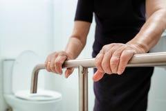 Elderly woman holding on handrail in bathroom. Elderly woman holding on handrail in toilet royalty free stock photo