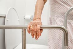 Elderly woman holding on handrail in toilet. stock photo