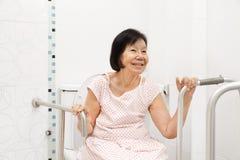 Elderly woman holding on handrail in toilet. stock photos